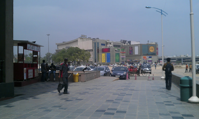 Rajouri Garden is one of the place which is well connected to various places in Delhi and have popular shopping places  as well !!! Rajouri has biggest Shopper's Stop in Delhi and other famous malls as well !!!Here is a photograph of biggest Shopper Stop in Rajauri Garden !!!Apart from Shopper's Stop, there are few malls adjacent to Metro Station !!!A man cleaning glasses of Shoppers Stop in Rajaouri Garden !!Here is a photograph of another Mall which is just diagonal to Shoppers Stop of Rajouri Garden !!!There are lots of options for folks who love shopping !!These malls are located conveniently next to the Rajouri Garden metro stop. The malls include, TDI Mall, TDI Paragon Mall, Shoppers Stop, City Square, West Gate Mall, and Paradise Mall. All of these malls are quite technologically advanced and feature great parking space and a nice ambiance. Rajouri Garden has risen a lot since these malls have been made.Surrounding areas to Rajouri Garden are Mayapuri , Tagore Garden, Subhash Nagar, Shivaji Enclave, Tilak Nagar, Shiv Nagar, Vishal Enclave, Ashok Nagar, Tihar Village, Hari Nagar and Shivaji Place.Metro has made this Rajouri Garden more accessible !!!