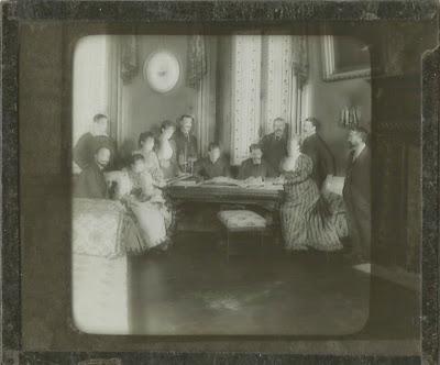 Eine Reihe von Damen und Herren in einem eleganten Salon im ausgehenden 19. Jahrhundert