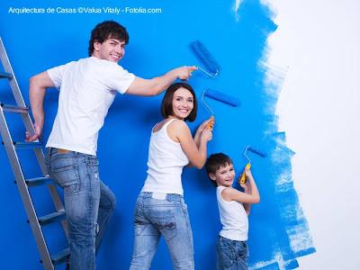 Una familia pintando de azul una pared