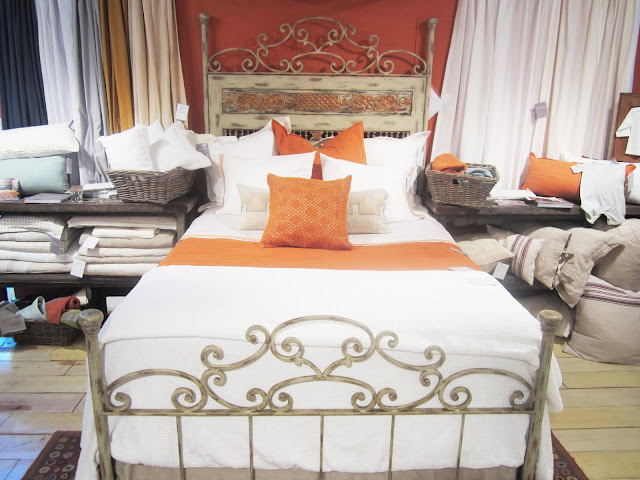 Pumpkin and white bedding by Coyuchi on a bed with a metal frame with a painted headboard and art deco details on the head and foot boards