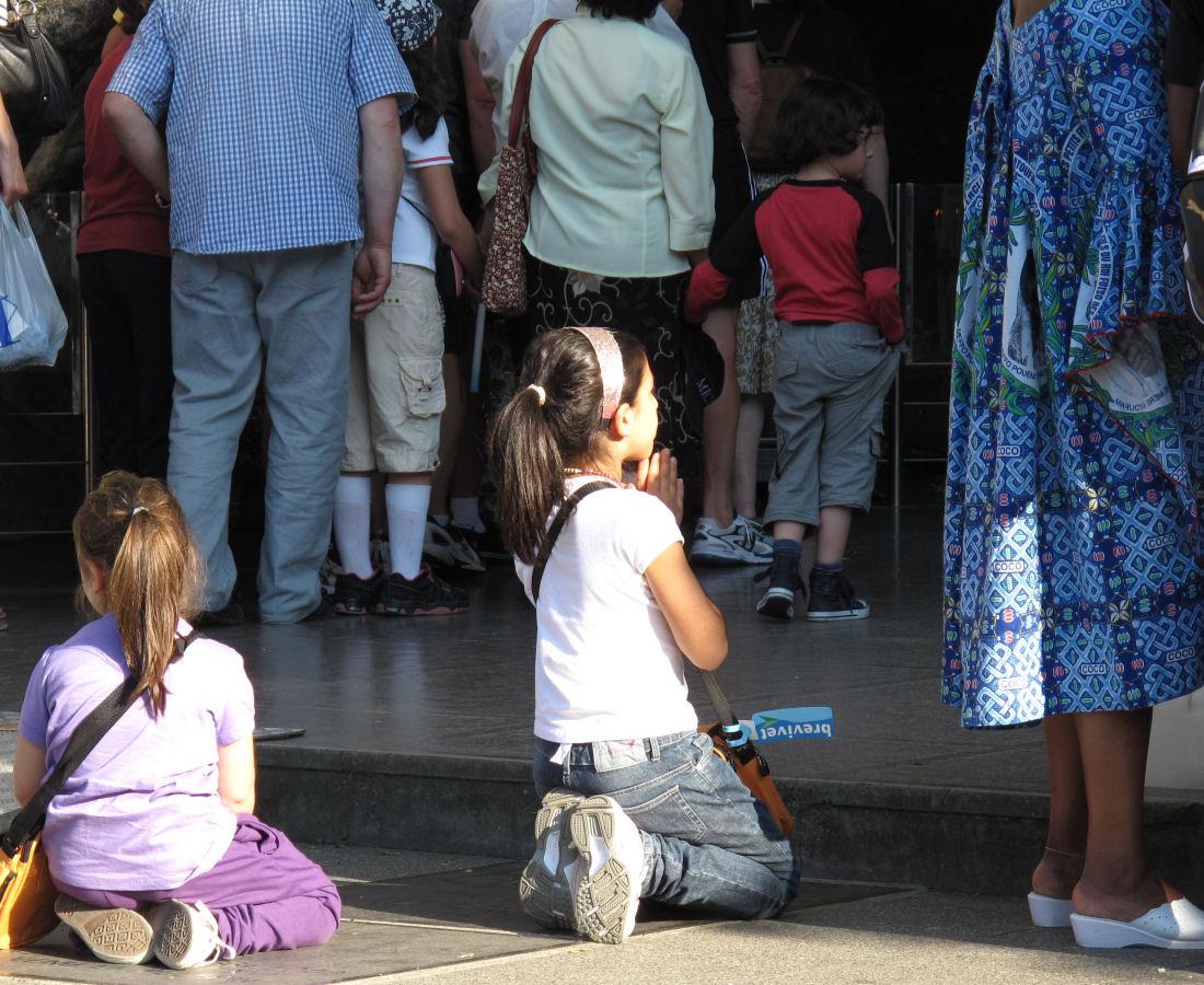 Crianças rezando diante da Gruta de Lourdes