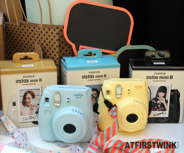 HEMA Instax mini 8 instant camera in pastel blue and yellow and colorful straps