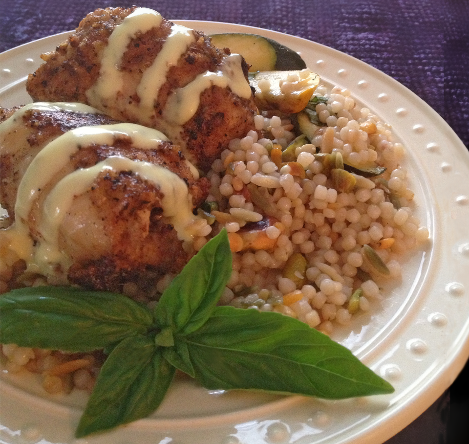 White plate with two chicken breast rolls prepared with couc-cous and squash
