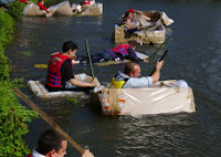 Boats Made Out Of Cardboard ON The Lake IN Reading with people in them