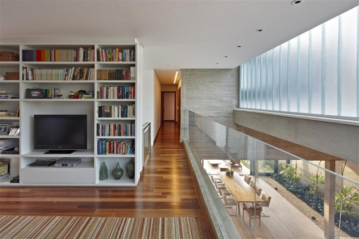 Book shelves and glass railing in modern home by Anastasia Architects