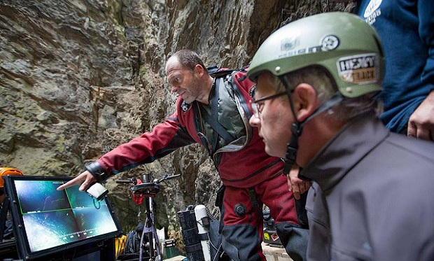 In this photo taken Sept. 27, 2016 in the flooded Hranicka Propast, or Hranice Abyss, in the Czech Republic Polish explorer Krzysztof Starnawski, left, and Bartlomiej Grynda, right, are reading images from a remotely-operated underwater robot, or ROV, that went to the record depth of 404 meters ,1,325 feet, revealing the limestone abyss to be the world's deepest flooded cave, during the 'Hranicka Propast - step beyond 400m' expedition led by Starnawski and partly funded by the National Geographic. (AP Photo/ Marcin Jamkowski)