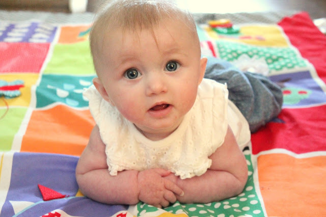 baby lying on tummy on play mat with arms crossed and head held high