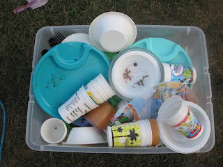 bin of reusable plastic cups and plates destined for the dishwasher after the party