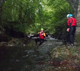 Man jumping into a deep pool whilst canyoning