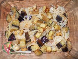 Colocar la cebolla y la berenjena en el fondo de la fuente de horno.