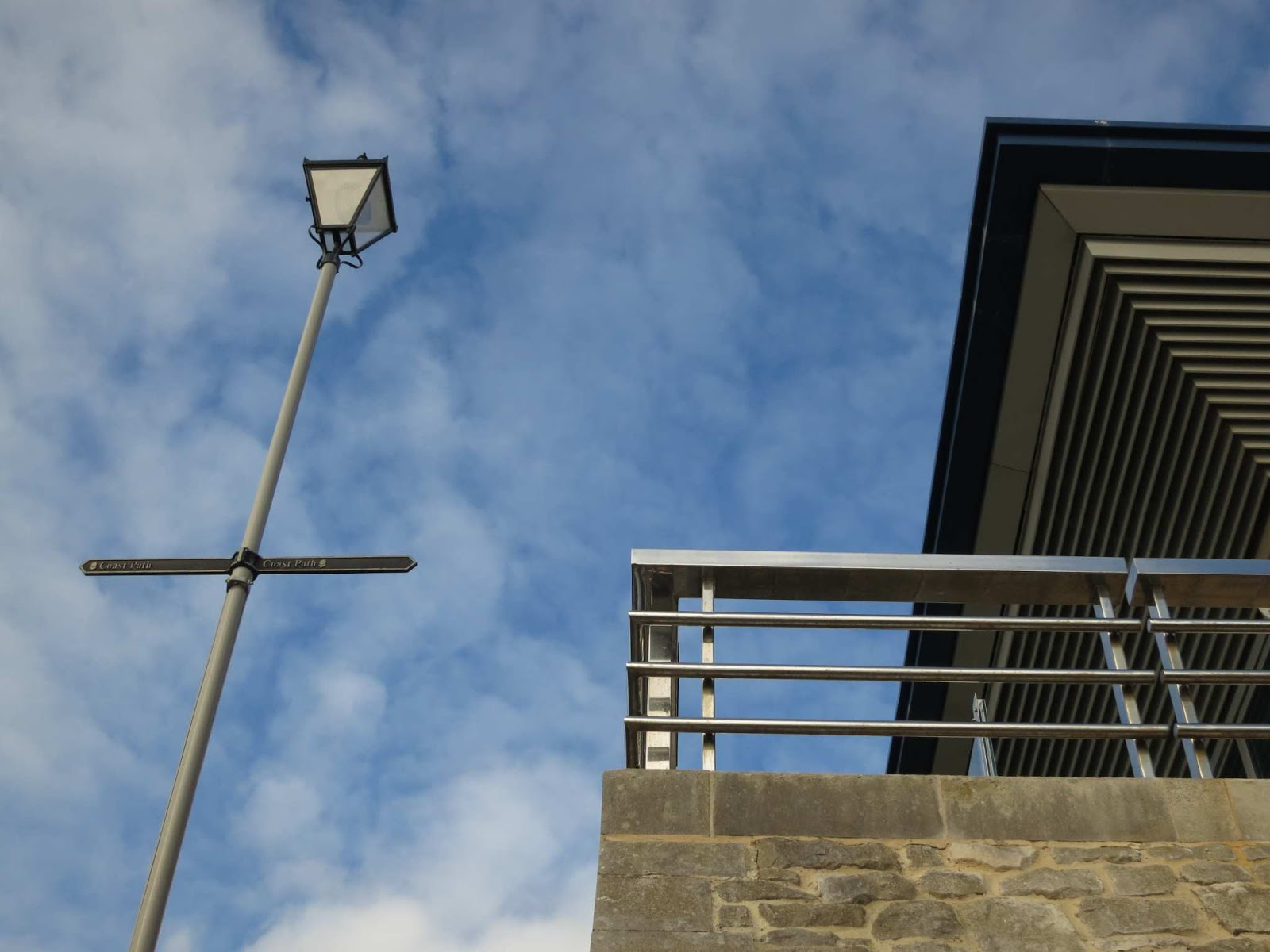 Lampost on left, rail and roof on right, sky behind.