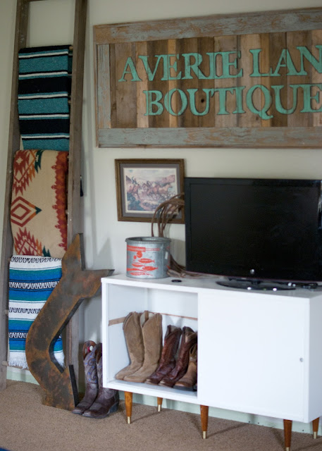 mcm cabinet, cowboy boots, metal arrow, ladder, mexican blankets, reclaimed wood shop sign