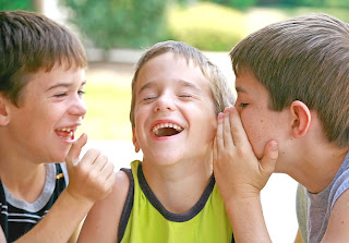 three little boys whispering and laughing