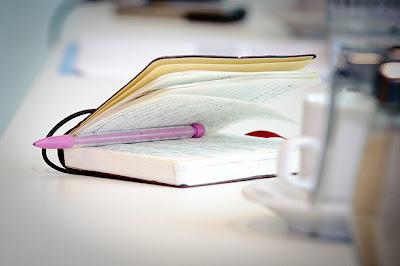 libreta moleskine semiabierta con un portaminas rosa en medio de sus páginas