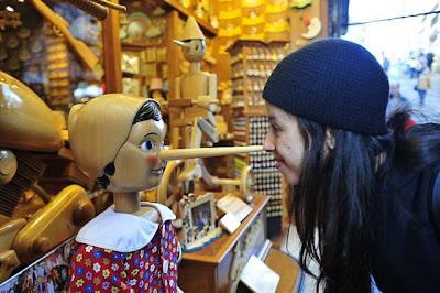 Na foto, Pinóquio, um boneco de madeira, encosta a ponta do longo nariz no nariz da sorridente Sara, uma menina de verdade, que veste casaco e gorro preto.