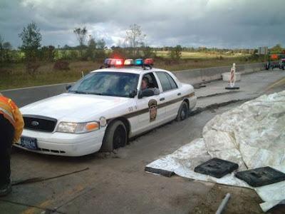 Drôle: voiture de police coincée dans le béton.