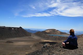 Jenn sitting cross-legged, looking at the crater lakes.