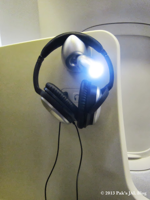 The reading light on the non-aisle side doubles as the headset holder
