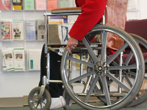 A woman in a wheelchair browses Stone-Hayes resources