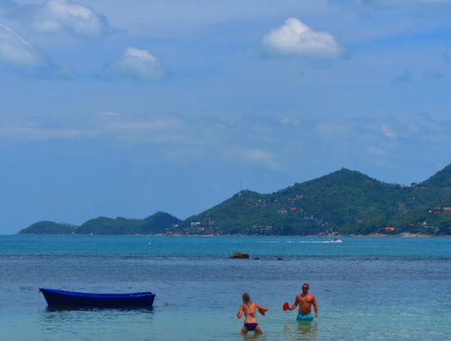 Beachgoers playing ping pong next to boat on Chaweng Beach