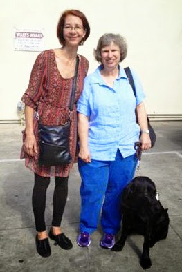 Graduate Marlene poses with her guide Lava (black Lab) with one of her puppy raisers