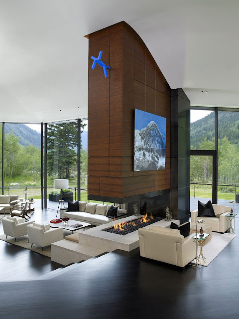 Living room of Aspen Residence by Stonefox with fireplace and big windows facing the forrest