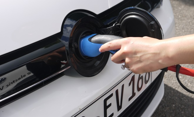 Plugging in to charge an electric car