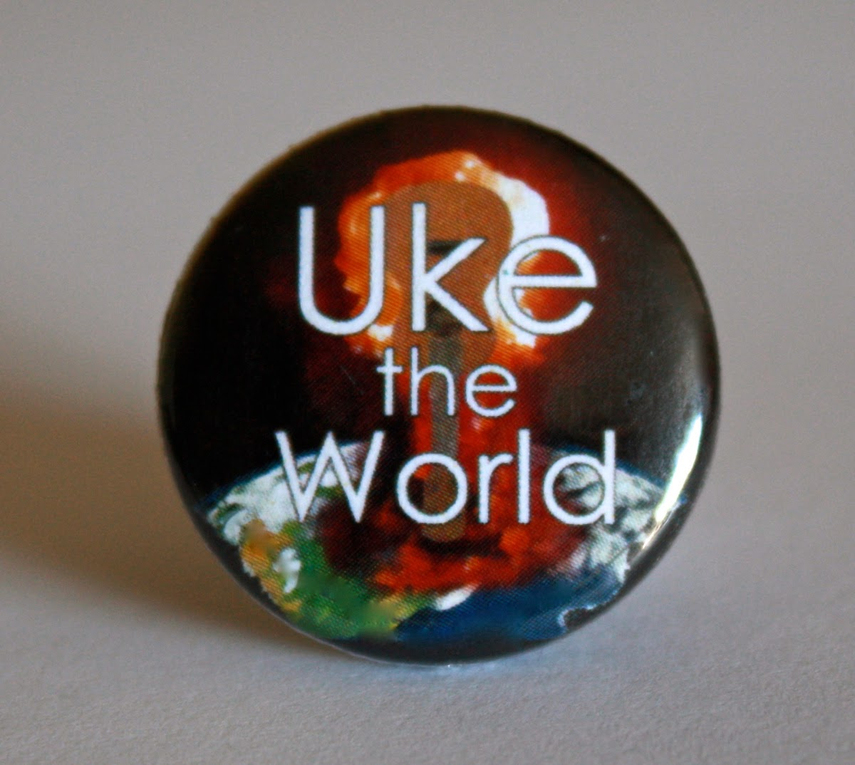 "A band button that says ""Uke the World"". There's a picture of a ukulele which is also a mushroom cloud."