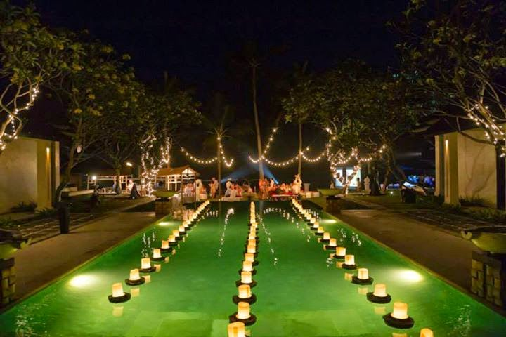 hanging bulbs over dinner area, floating candles above the pool, fairy lights on trees