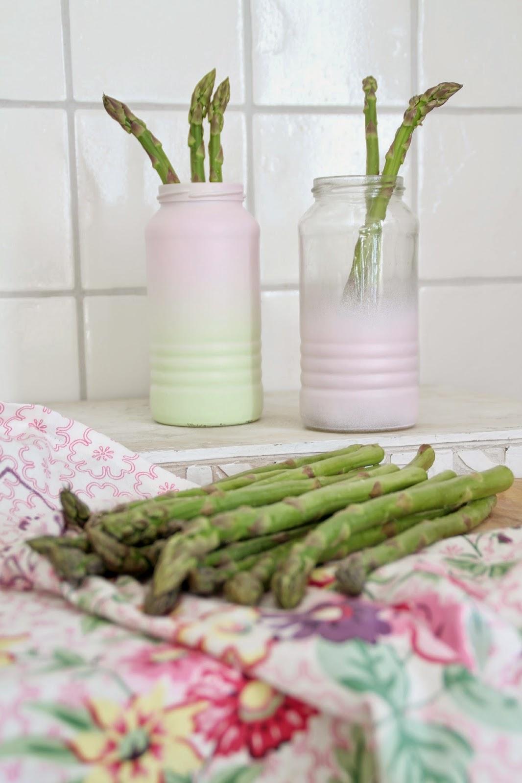Pastellige Bohnengläser mit Spargel statt Blumen im Hintergrund im Vordergrund Spargel auf einem blumigen GreenGate Geschirrtuch