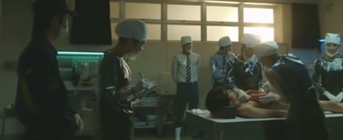 The police observe as Higa performs an autopsy.