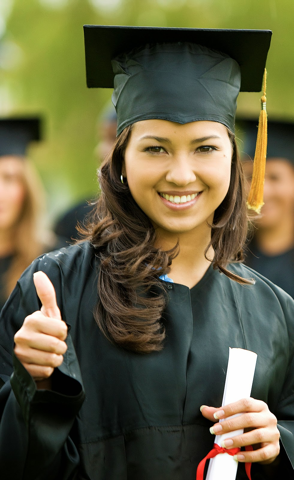 picture of a female college graduate giving the thumbs up