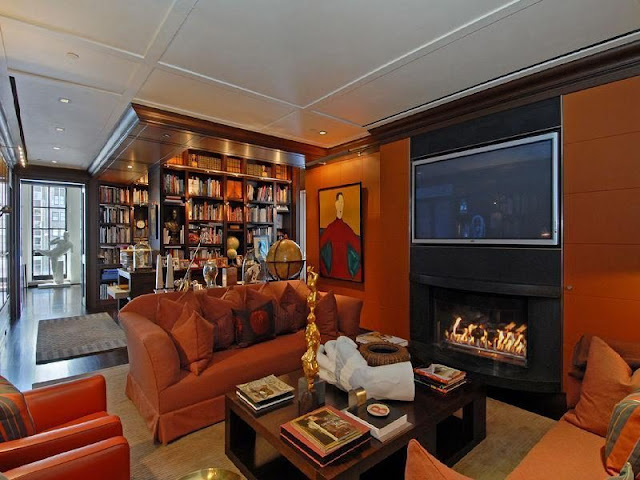 Photo of sitting area in the private library with brown sofas and fireplace