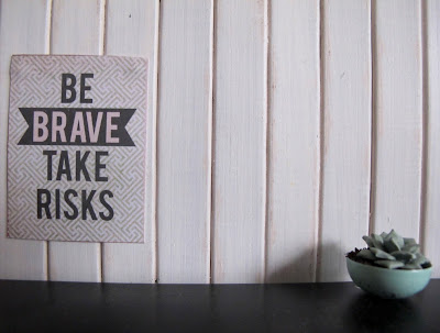 A modern dolls' house miniature scenewith a poster saying 'Be brave take risks, and a succulent in a bowl.