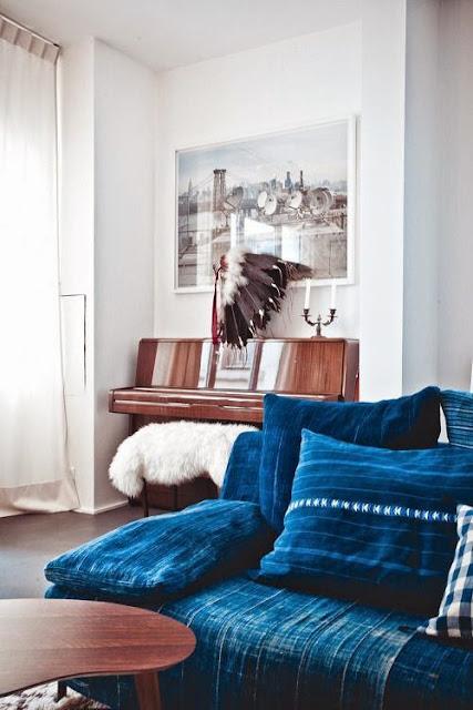 Brązowe pianino w tle kanapy w kolorze indygo