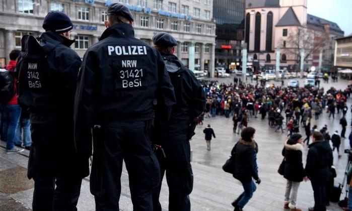 Polícia alemã observa grupo de imigrantes sírios perto da principal estação ferroviária de Colônia.