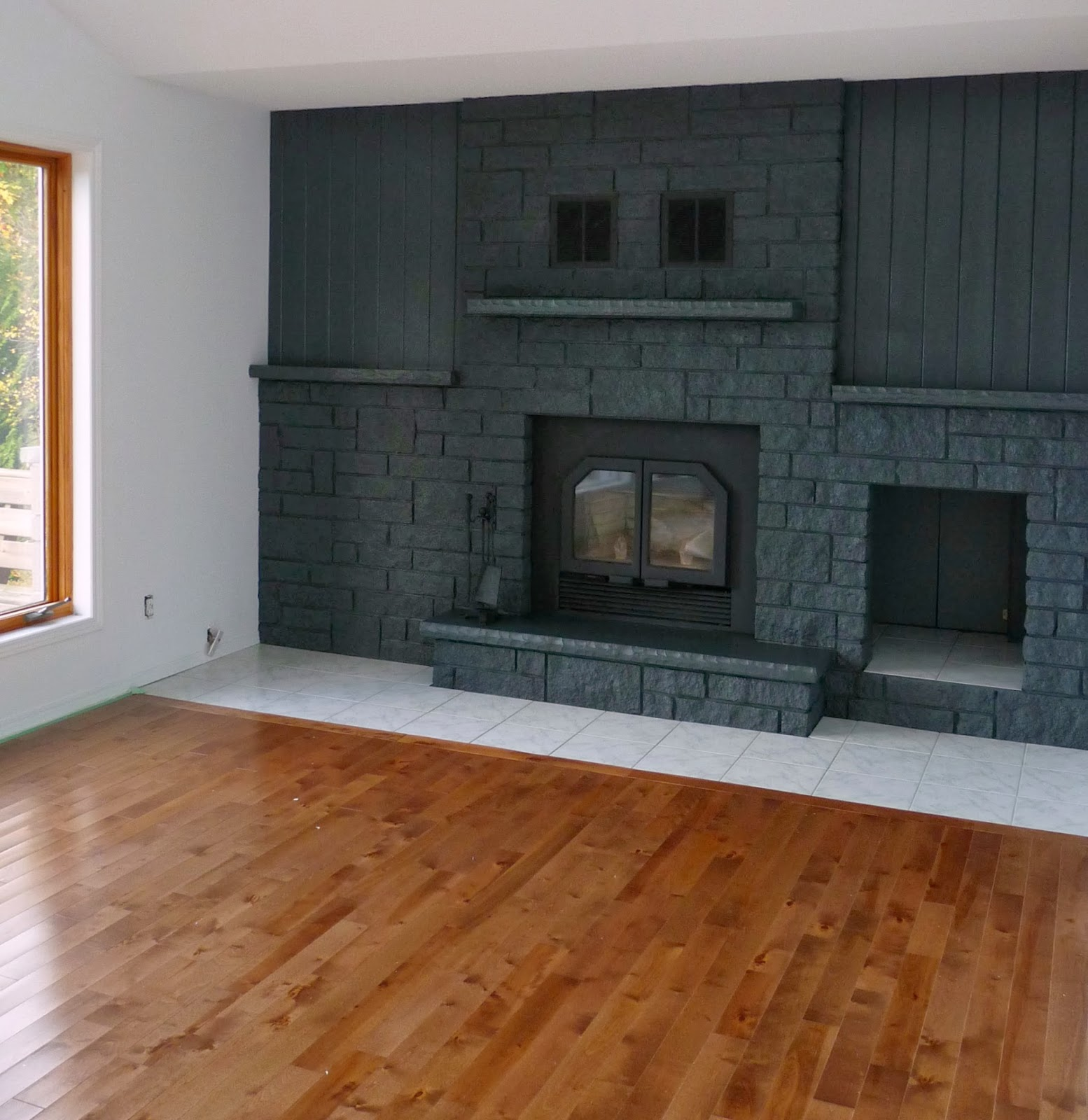 Dark grey fireplace, warm wood floors