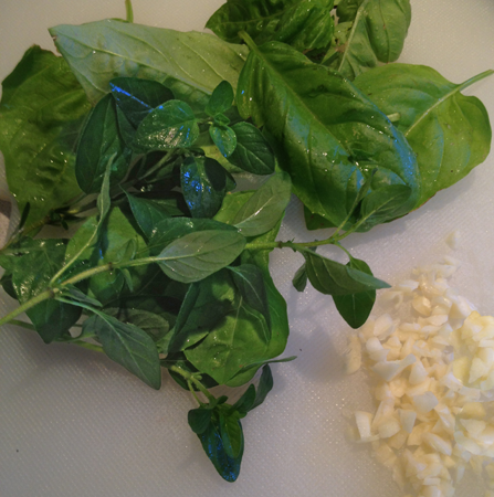 Image shows fresh oregano and basil next to chopped parsely. Before being aded to mortar bowl.