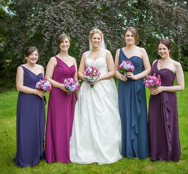 ALison the bride and her bridesmaids pose for photographs in the gardens. classic hairstyling to compliment their elegant gowns
