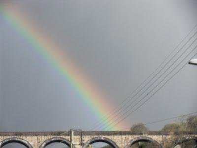 A rainbow over a railway bridge