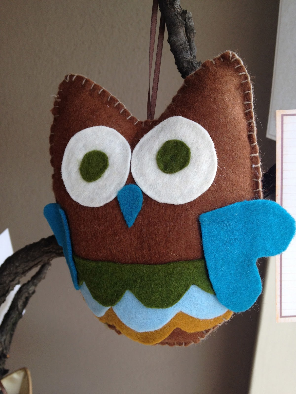 felt owl hanging in a tree