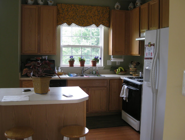 A 90's kitchen with oak cabinets and white appliances - before.