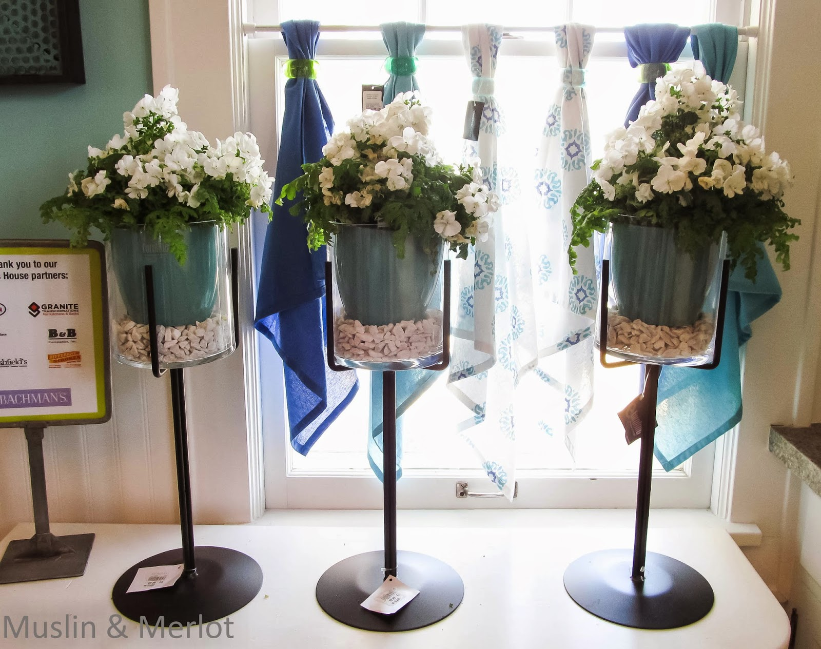 Dishtowels & napkin rings window treatment. The plant pots are being help up by candle-holders.