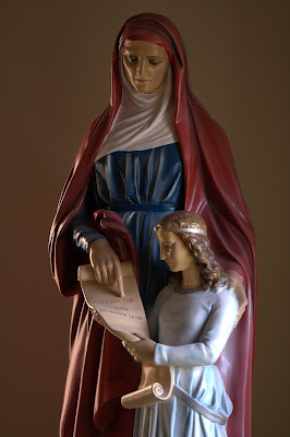 Window lit statue of St. Anne Mother of Mary and the Virgin Mary with scroll with Latin inscription Egredietur virga de radice Jesse