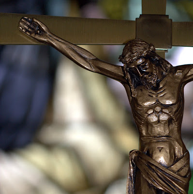 Close-up of bronze crucifix with stained glass window in the background