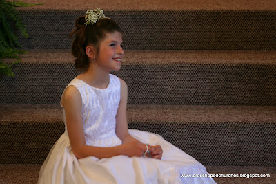 Granddaughter Emily sitting on steps in white Communion dress.