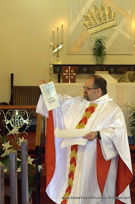 Priest passing out certificates.