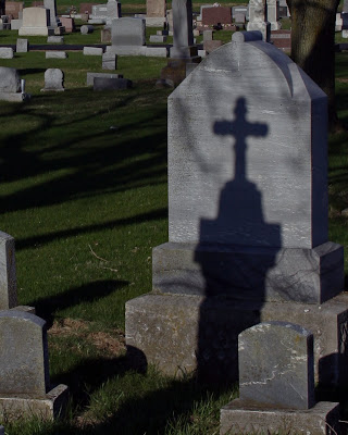 Old cemetery tombstone with shadow of cross.