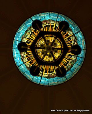 Celing round stained glass window with hanging chandaler in the middle.