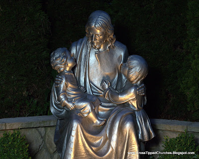 Statue of Jesus holding children lit by spot light.